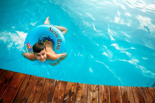 chlapec s nafukovacím kruhem v bazénu